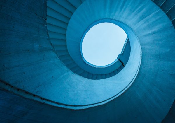 Abstract blue building spiralling up to sky